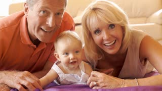Grandparents and baby granddaughter lying on floor looking at camera.