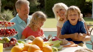 Grandparents and grandchildren playing and sitting at table of food in garden.