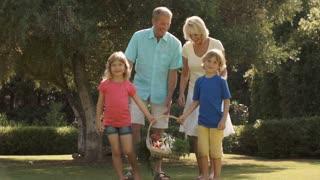 Grandparents and grandchildren walking in garden with basket of vegetables.