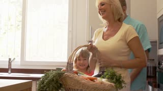 Grandparents and granddaughter in kitchen with fresh vegetables in basket.