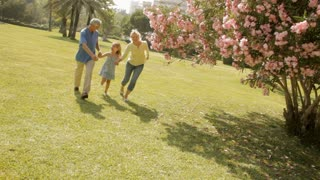 grandparents and granddaughter running in park