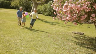 grandparents and granddaughter running with balloons in park