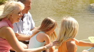 Grandparents and two granddaughters fishing with net in pond in park.
