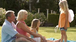 Grandparents and two granddaughters playing in park with magic wand.