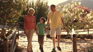 Grandson and grandparents walking towards camera in park.