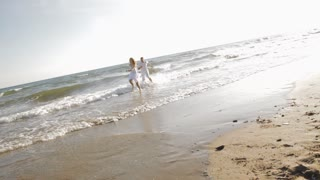 hand held shot of young couple running and chasing on beach