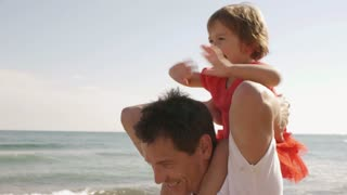Happy little girl on her father's shoulders at beach.