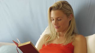 Happy woman reading book in bed.
