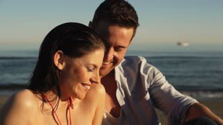 Head and shoulders dolly shot of young couple sitting on beach.