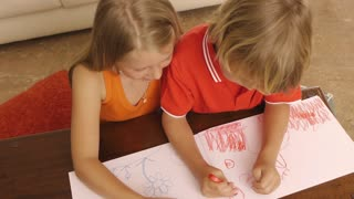High angle shot of brother and sister coloring together.