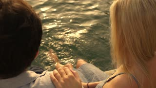 High angle shot of couple sitting at water's edge.
