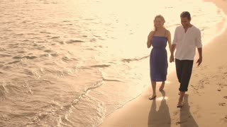 High angle shot of couple walking on beach.