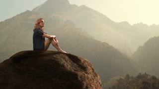 Hiker sitting on rock in countryside.