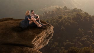 Hikers resting on huge rock in countryside.