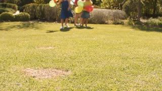 Lift up of three girls running towards camera with balloons.