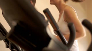 Lift up shot of couple exercising on treadmill at gym.