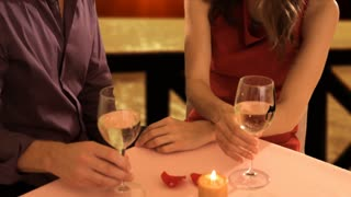 lift up shot of mid aged couple at dinner toasting camera