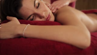 lift up shot of young woman having massage, candlelit background