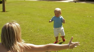 Little boy running into mother's arms in park.