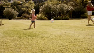 Little girl and mother playing with ball in park