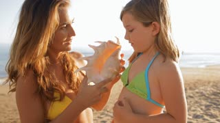 little girl and mother with seashell on beach