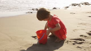 Little girl playing in the sand at the beach.