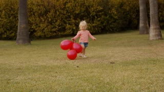 Little girl running to camera with red balloons in park