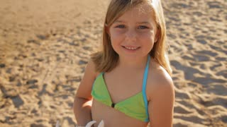 little girl with seashell on beach