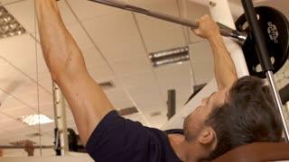 Man lifting weights at gym.