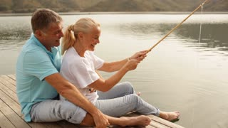 Mature couple fishing by lakeside