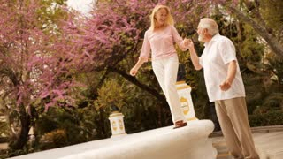 Mature couple in park walking on fountain wall