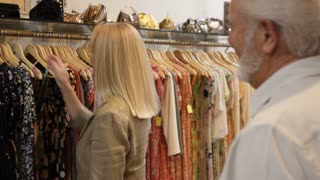Mature couple in shop looking at dresses