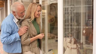 Mature couple in town, looking in shop window