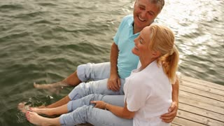 Mature couple playing by lakeside