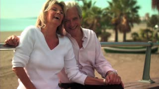 Mature Couple sitting by Beach