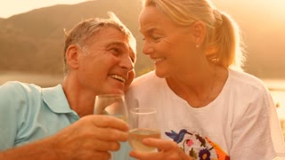 Mature couple sitting in countryside in sunset with wine