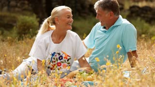 Mature couple sitting in countryside