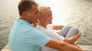 Mature couple sitting on jetty by lakeside