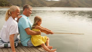 Mature couple with grandchild fishing by lakeside