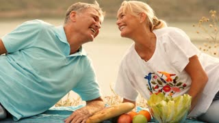 Mature couple with picnic in countryside
