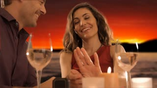 mid aged couple at dinner giving ring