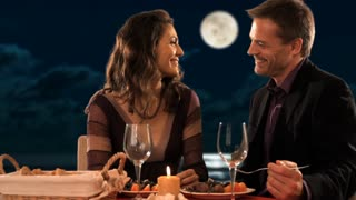 mid aged couple at dinner waiter pouring wine
