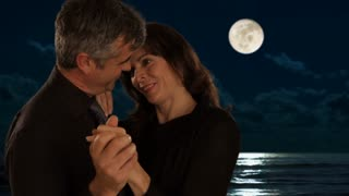 mid aged couple dancing in moonlight