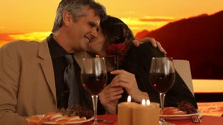 mid aged couple dining in sunset