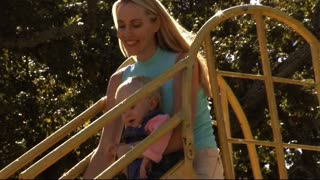 Mother and Baby in Park on slide