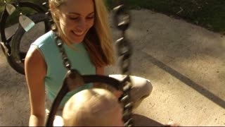 Mother and Baby in Park on swing