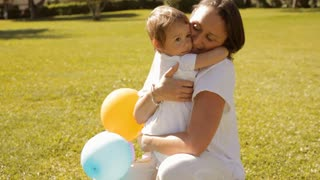 mother and baby in park playing with balloons