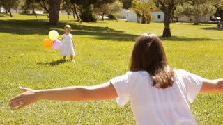mother and baby playing with balloons in park