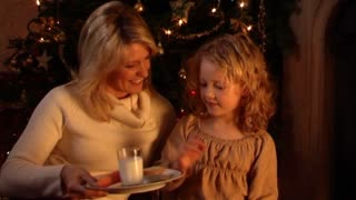 Mother and daughter at Christmas putting out glass of milk for Santa.