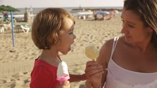 Mother and daughter eating popsicles at the beach.